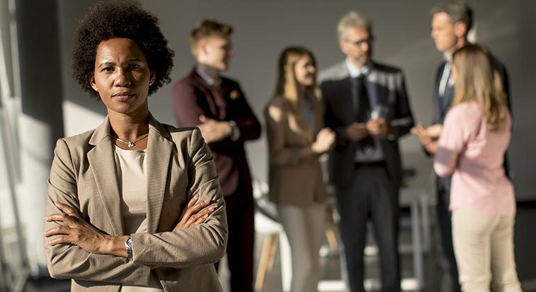 Svart kvinna i kontorsmiljö med kollegor i bakgrunden.